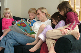 [Several children sitting on a sofa with their mother, reading a book together.]